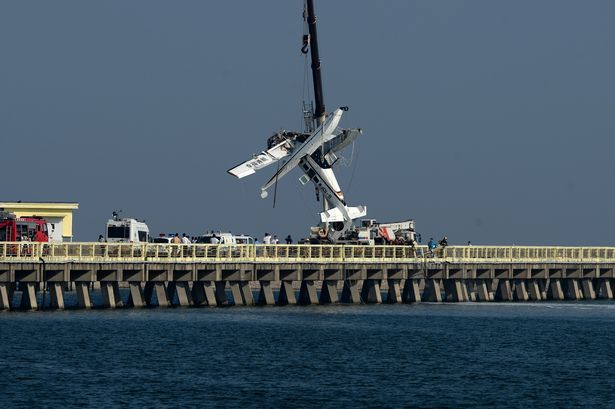 a plane wreckage being lifted by a crane in china