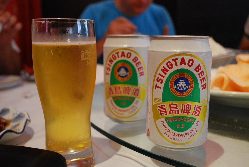 tsintao beer in cans and a glass