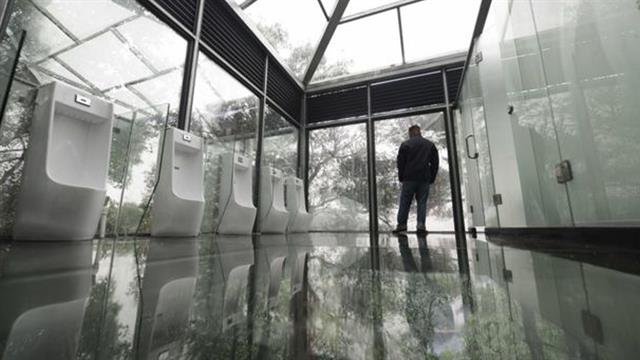 a man standing in a glass bathroom in china