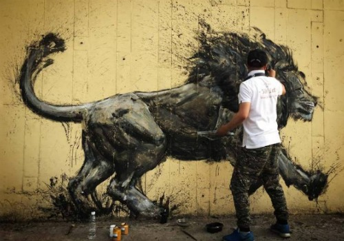 a man spray painting a lion an a wall in china