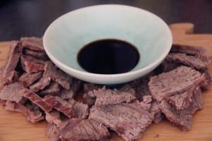 a bowl of soy sauce surrounded by boiled beef