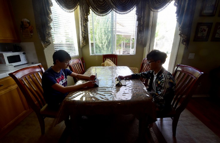 two boys sitting across from each other at a table