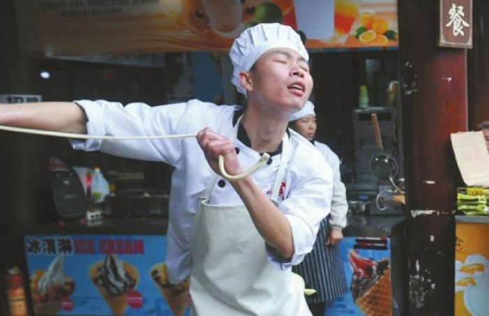 a chef in china dancing while making noodles