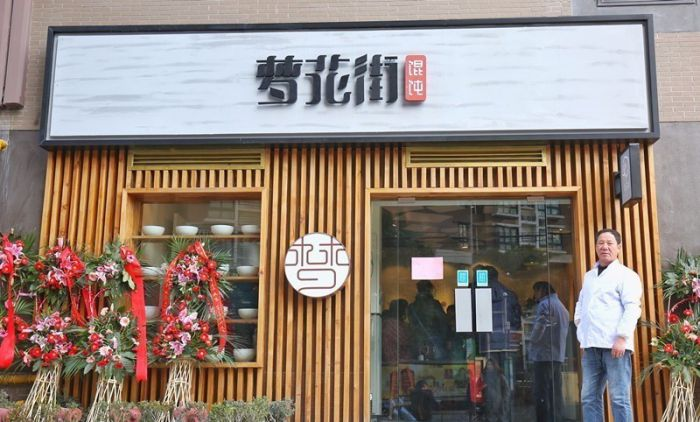 a man standing outside a wonton restaurant in shanghai