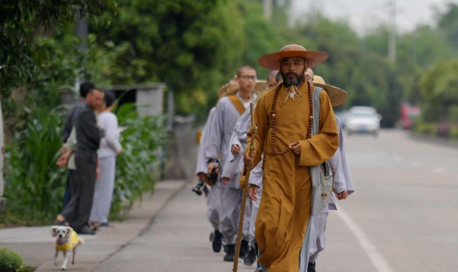 monks walking along a road in single file in china
