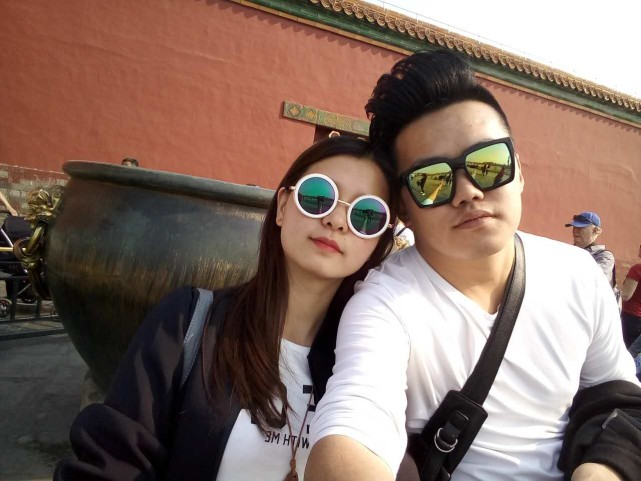 chinese couple taking a selfie at forbidden city in beijing