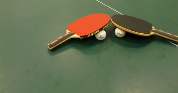 table tennis bats and balls on the table