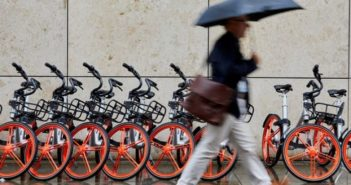 man with umbrella walking past mobikes in uk