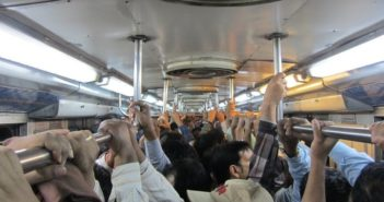 people holding bars in a metro carriage in india