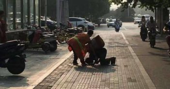 beggar kneeling to sanitation worker in china