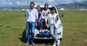 family photo in front of a car in a field