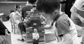 side view of boy playing with building blocks