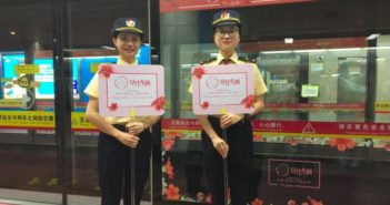 two station workers holding signs for women only section in guangzhou metro