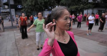 women square dancing with earphones in china