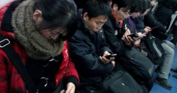 people using phones on metro in china
