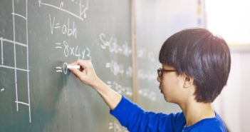 side view of boy doing maths on blackboard