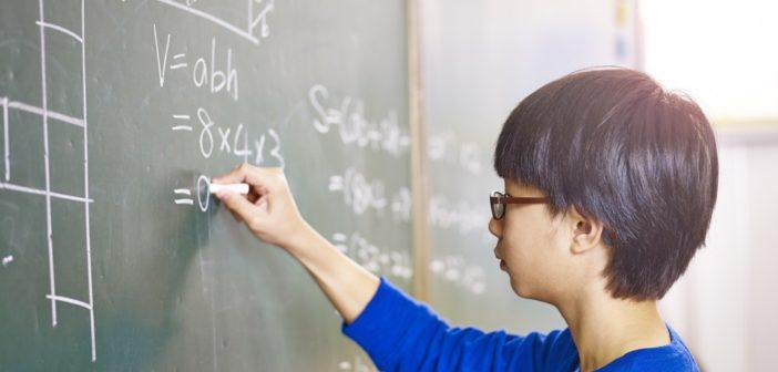 side view of boy doing maths on blackboard