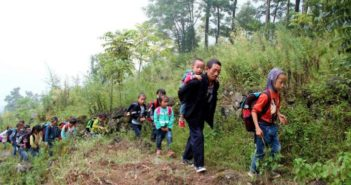 man leading children through woods to school in china