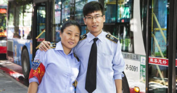 mother and son posing for picture at work as bus drivers