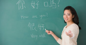 teacher teaching chinese characters on a chalk board