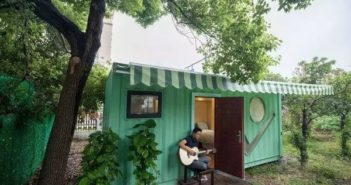 man playing guitar outside shipping container home in china
