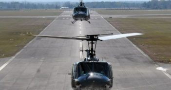 front view of two helicopters above a runway