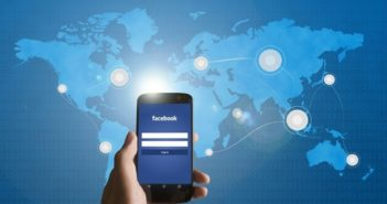 facebook on phone in front of world