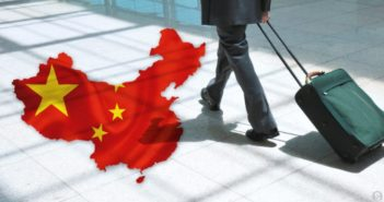 businessman arriving with luggage next to china flag