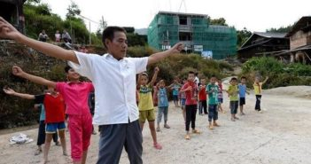 teacher leading students in exercises at mountain school in china