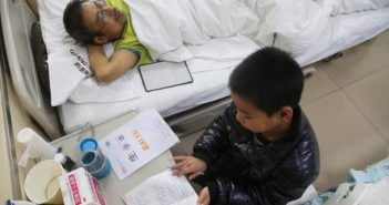top view of boy next to father in hospital bed