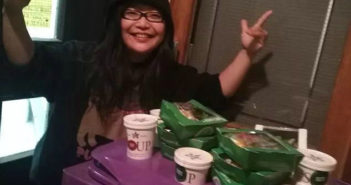 girl posing for picture next to food on top of a bin