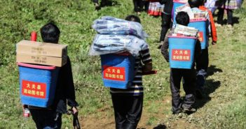 back view of children carrying books up a mountain in china