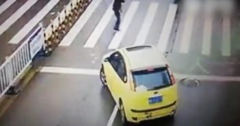 yellow car waiting at zebra crossing in china