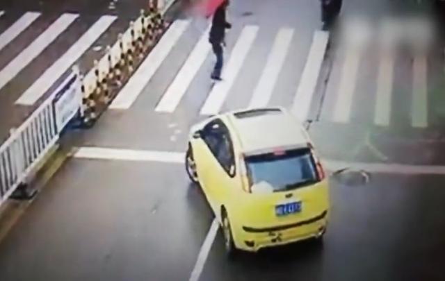 yellow car waiting at zebra crossing in china