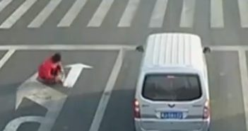 man painting arrow on road in china
