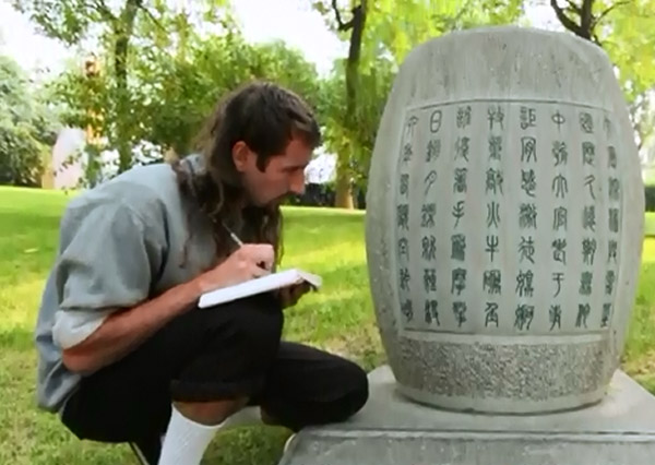man crouching with notebook next to characters on stone