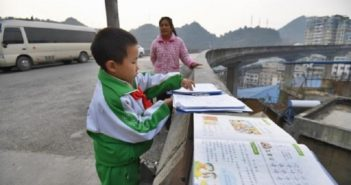 young boy doing homework on overpass in china