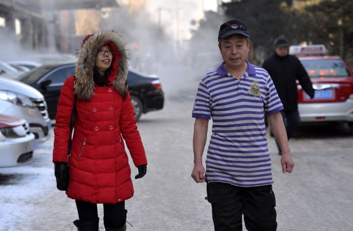 two people walking down the street in shenyang