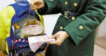 customs officer with child who has a lot of money in bag