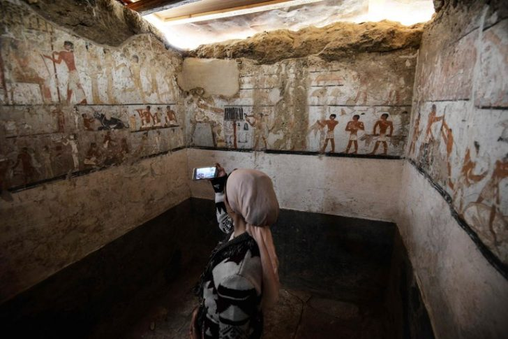 woman taking pictures inside tomb in egypt