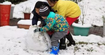 children building a snowman in china