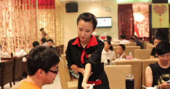 waitress serving customers at restaurant in china