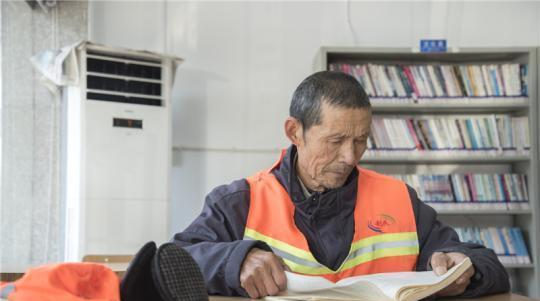 sanitation worker reading in a library in china