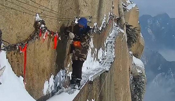 man walking along cliff cleaning snow