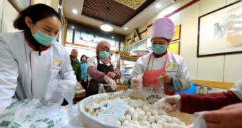 workers making sticky rice dumplings for lantern festival at shop in china