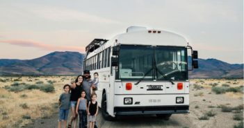 family with a school bus in the desert