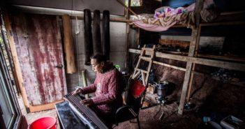 man playing guqin at home in china