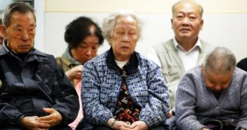 five elderly asian people sitting together in a room
