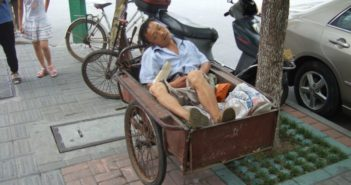 man sleeping in back of cart on street in china