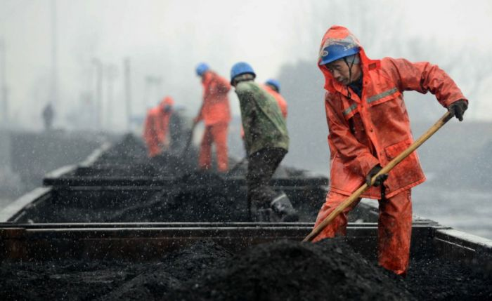 workers loading coal onto railcars in china